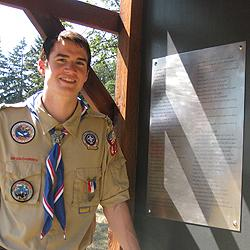 Eagle Scout Len Castro stands by kiosk he built to memorialize settlers.