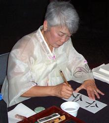 Patsy Suhr O'Connell, demonstrating traditional Korean calligraphy.
