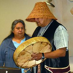 His wife Annette beside him, Merlin Bullchild performs a traditional welcoming song.