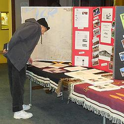 Audience member examines displays of tribal history and artifacts.