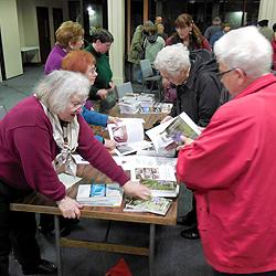 After the program, audience members flock to the table to get their signed first editions.