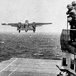Witnessing a first. Anxious crew members watch as a plane never intended to be launched from a carrier struggles into the sky.